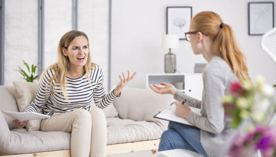 Angry woman screaming while sitting on beige settee during therapy with psychiatrist. Psychotherapy concept.